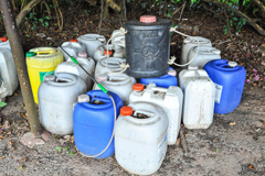A collection of coloured containers of household chemicals and poisons kept insecurely in a garden