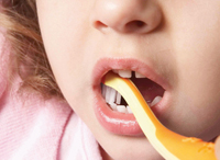 Toddler having the chewing surfaces of her teeth cleaned by an adult