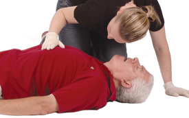 Woman placing her hand on a patient's chest and placing her cheek over man's mouth to check for signs of man breathing.