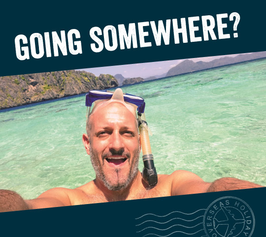 man taking a selfie while snorkelling at an exotic beach, titled with 'Going somewhere'