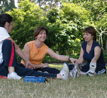 Three women performing stretching exercises in a park