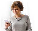 Woman in grey shirt on looking at smart phone