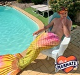 man sitting by backyard pool wearing a mermaids tale