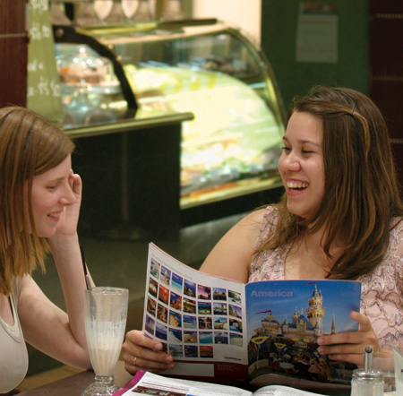 Two women in a cafe laughing and reading a travel brochure