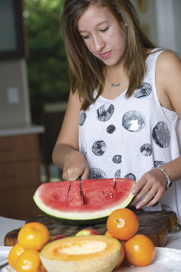 Lady cutting up a watermelon
