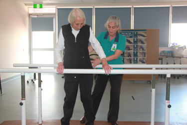 A health care professional helping person leaning on a bar during therapy