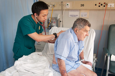 Health care professional with stethoscope placed on patient's back
