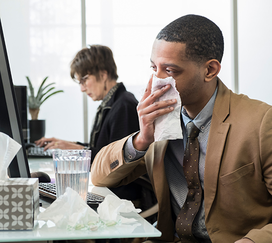 man with cold covers face with a tissue
