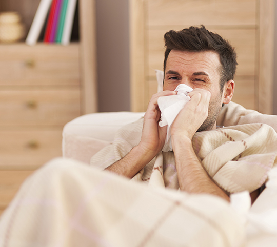 man with a cold blowing nose