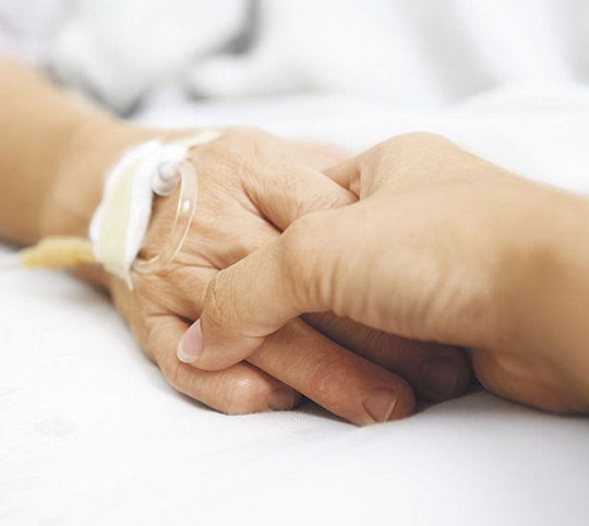 Person holding patients hand in hospital