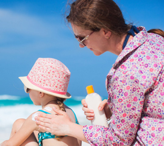 Mum putting sunscreen on daughter at the beach