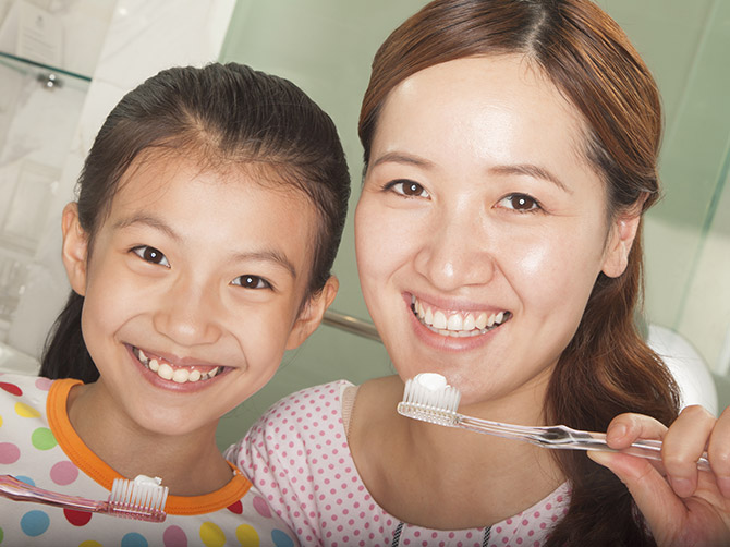 Mother and daughter holding toothbrushes with toothpaste