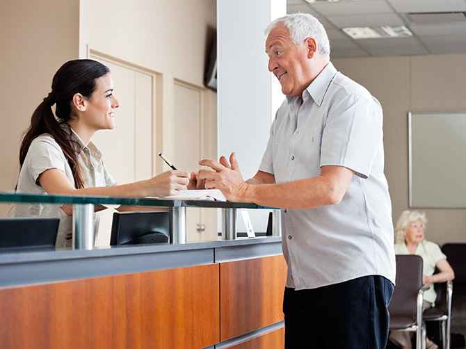Man in his 60s talking to a receptionist in a doctor's practice