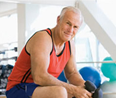 Senior in a gym sitting on an exercise ball and holding a dumbbell