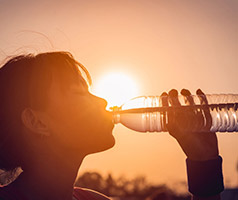 Woman drinking a bottle of water outside in the hot sun