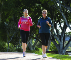 Two women running along a path in a park