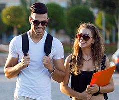 Two uni students walking next to each other wearing backpacks and holding files
